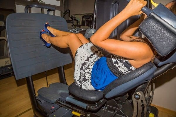 Woman in Dress and Heels Doing Legpress Workout at Gym