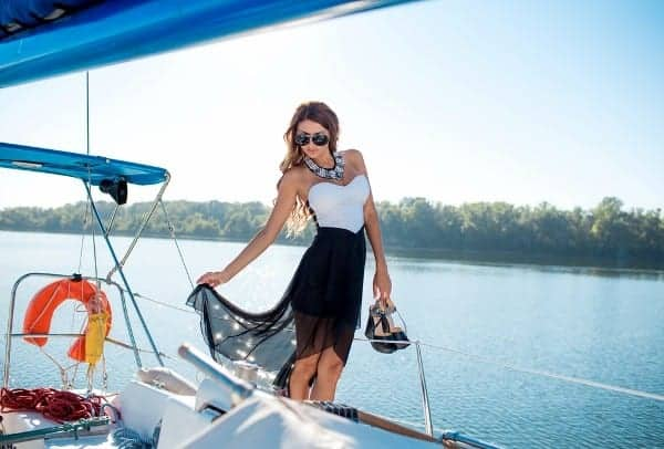 woman-in-summer-dress-standing-on-a-yacht