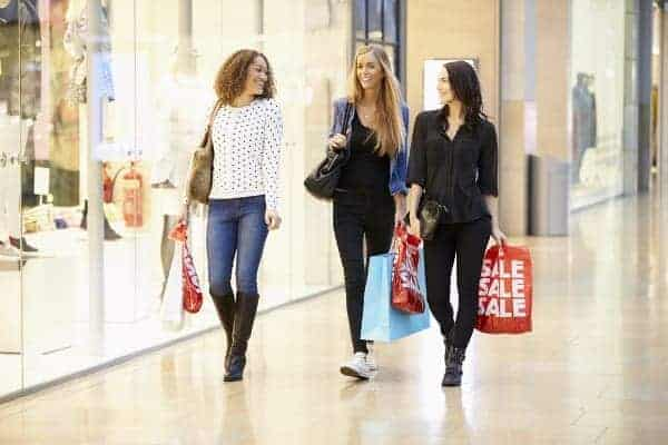 Three Women Friends Shopping In Mall Together Holding Bags